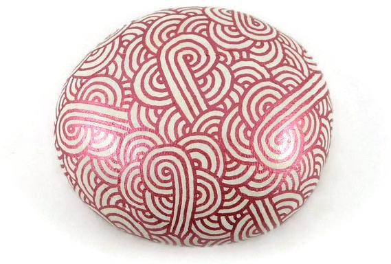 Galet peint blanc aux volutes rose fuchsia métallisées